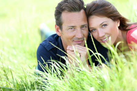 Loving couple laying in country field photo