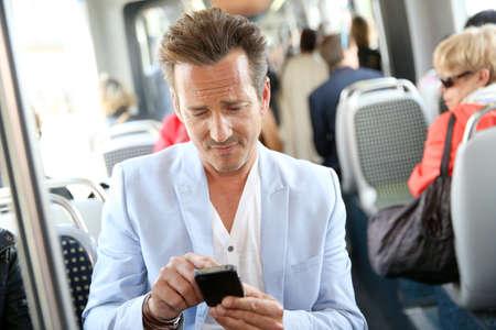 streetcar: Mature man using smartphone in streetcar Stock Photo