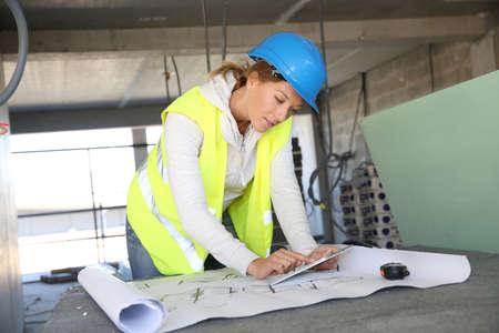 arquitecto: Arquitecto de la mujer en la obra de construcción que usa la tableta