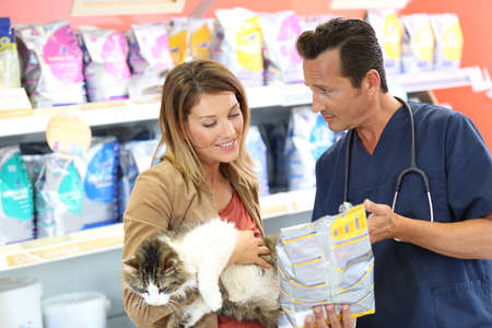 Veterinarian showing pet food to client Stock Photo