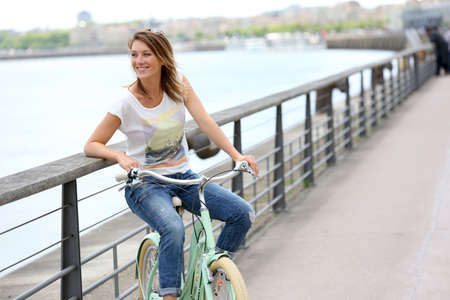Woman with bicycle relaxing by river Standard-Bild