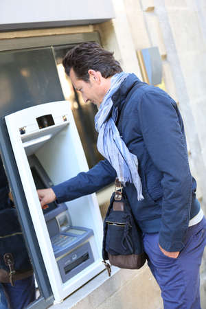 Man withdrawing money from ATM machine photo