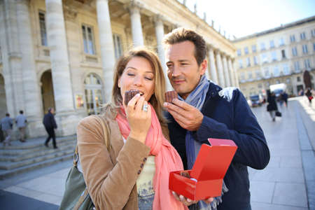 Couple in Bordeaux eating canelés, typical pastry photo