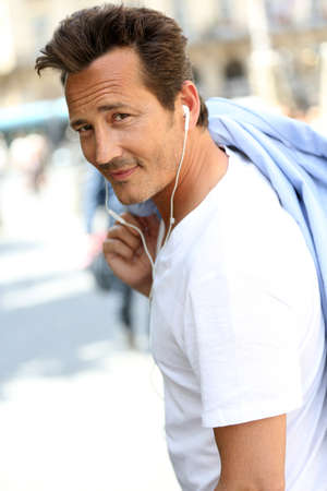 Trendy handsome man talking on phone with handsfree photo
