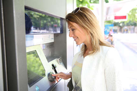 withdrawing: Woman withdrawing money from ATM machine Stock Photo