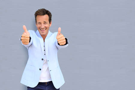 Cheerful mature man showing thumbs up photo