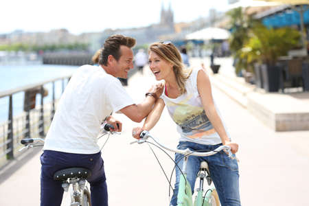 Cheerful couple riding bikes in Bordeaux photo