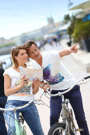 Couple reading map on bike tour photo