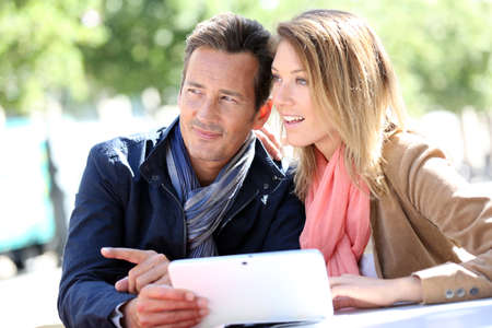 websurfing: Couple websurfing with tablet in town Stock Photo