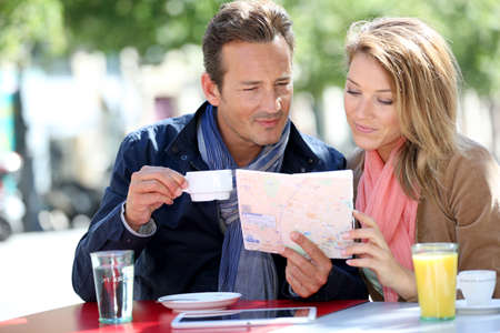 Couple of tourists reading city map photo