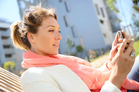 Woman relaxing in park and using smartphone photo