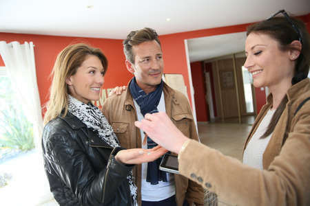 Real estate agent giving house keys to clients photo