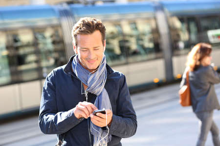 handsfree phone: Man in town talking on the phone with handsfree