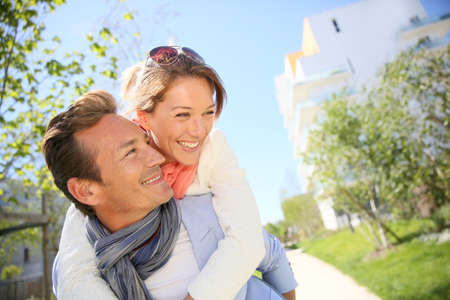 Man giving piggyback ride to woman in park photo