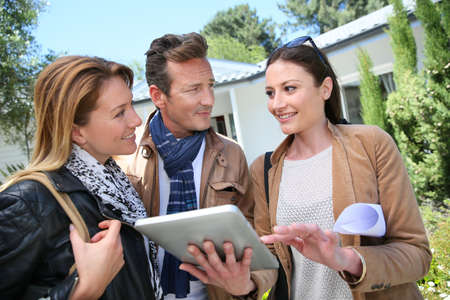 realestate: Real-estate agent with tablet showing house to clients Stock Photo