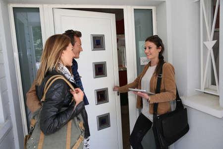abriendo puerta: Pareja casa de visita con el agente de bienes raíces