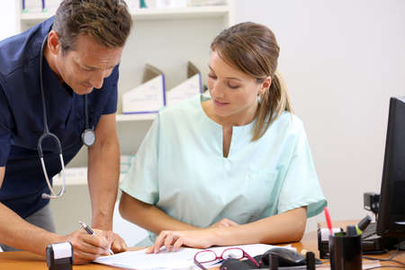 Nurse having doctor signing prescription photo