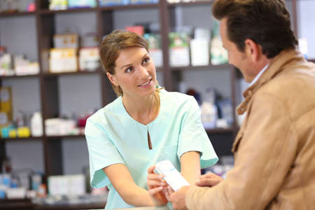 advice: Pharmacist giving advice to customer on medication