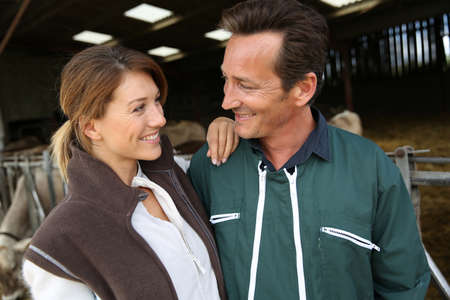 Cheerful couple of breeders standing in barn photo