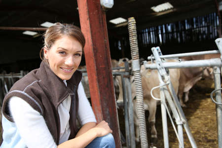 Smiling breeder woman standing in barn photo