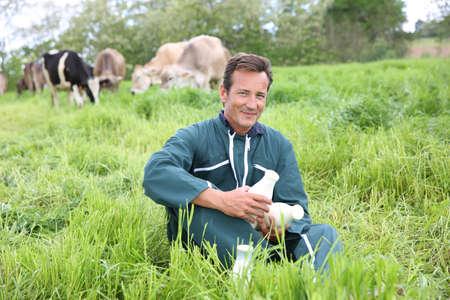 Farmer in field holding bottles of milk photo