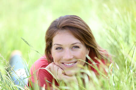Beautiful smiling woman laying in country field photo