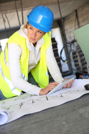 Woman architect on building site using tablet photo