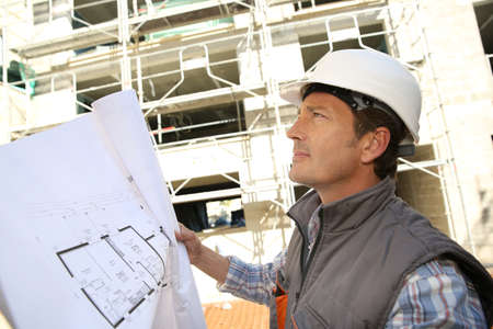 Construction manager on building site holding blueprint photo