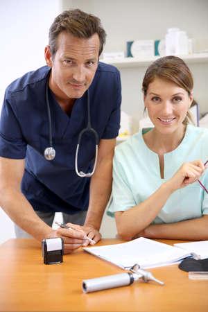 medicalcare: Nurse having doctor signing prescription