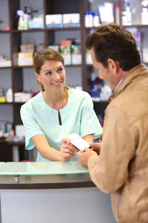 Pharmacist giving advice to customer on medication photo