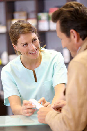 Pharmacist giving advice to customer on medication photo