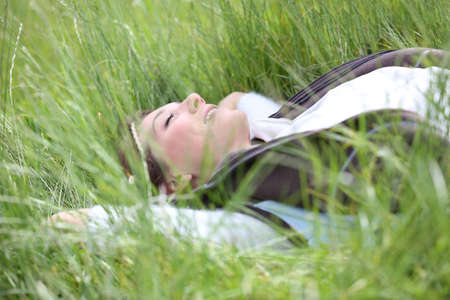 Woman relaxing in country field by sunny day photo