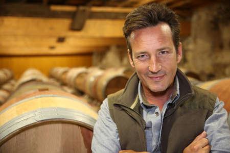 winemaker: Portrait of winemaker standing in wine cellar