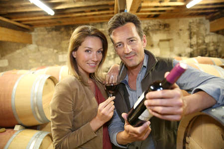 Cheerful couple of winegrowers in wine cellar photo