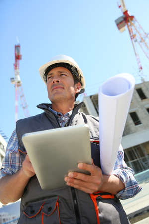 albañil: Empresario en el sitio de construcción que usa la tableta