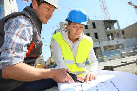 Ingenieurs op bouwterrein controleren plannen Stockfoto
