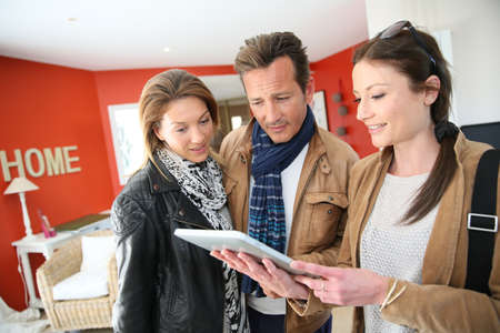 modernity: Real-estate agent showing house project on tablet