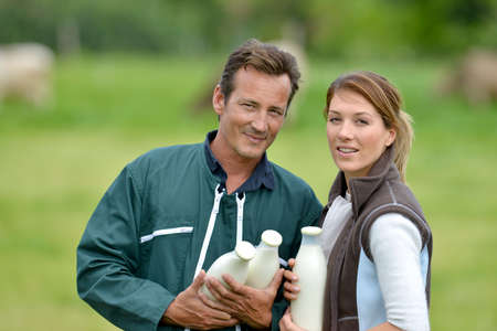 Couple of farmers in field holding milk bottles photo