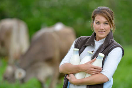 Smiling breeder woman holding bottles of milk photo