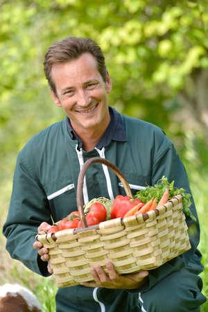 Farmer in garden holding basket of fresh vegetables photo