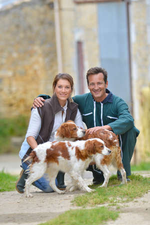 Couple of farmers with dogs around farm house photo