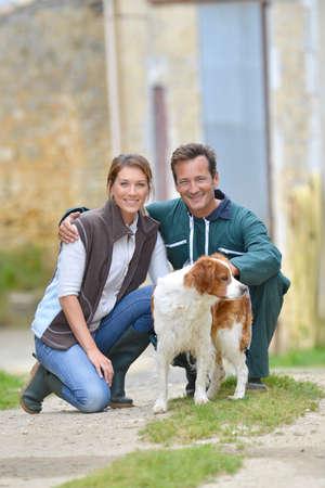 farm house: Couple of farmers with dogs around farm house Stock Photo