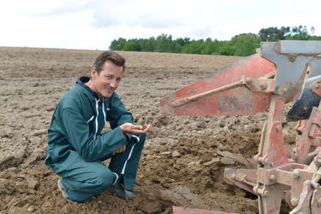 Farmer checking on cultivated ground quality photo