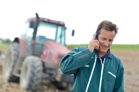 granjero: Granjero que recorre en el campo y hablando por teléfono móvil