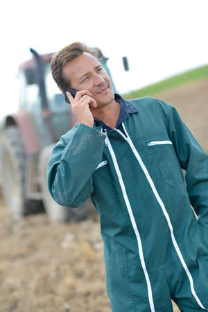 phonecall: Farmer walking in field and talking on mobile phone