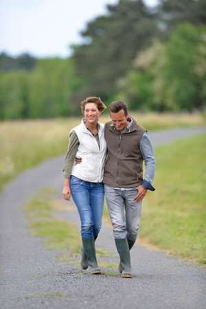 breeder: Cheerful 40-year-old couple walking in countryside
