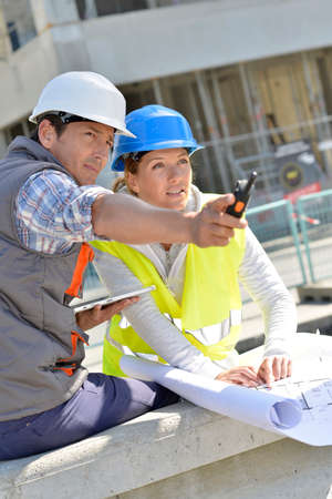 Engineers on building site checking plans photo