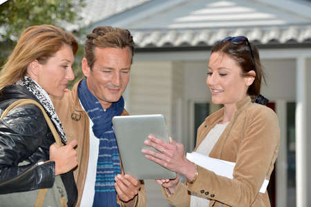 Real-estate agent with tablet showing house to clients photo
