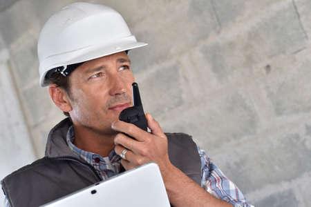 Entrepreneur on building site using walkie talkie photo