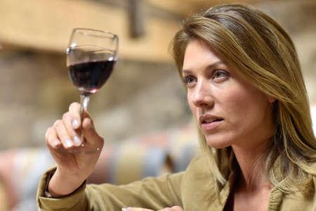 Woman tasting red wine in cellar